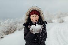 Η γελώντας γυναίκα έντυσε το θερμό βγάζοντας από τη θέση που ήταν χιόνι από τα χέρια της Στοκ Φωτογραφία