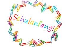 """Η γερμανική λέξη για """"πίσω στο σχολείο """"που πλαισιώνεται από τους ζωηρόχρωμους συνδετήρες εγγράφου στοκ φωτογραφία"""