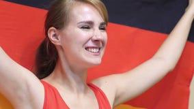 Η γερμανική νέα γυναίκα γιορτάζει το κράτημα της σημαίας της Γερμανίας σε σε αργή κίνηση απόθεμα βίντεο