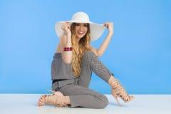 Η γελώντας όμορφη νέα γυναίκα στο άσπρο καπέλο ήλιων κάθεται στο πάτωμα Στοκ Εικόνες