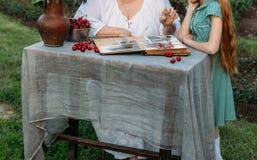 Η γιαγιά κάθεται στον πίνακα με την εγγονή της, της παρουσιάζει παλαιό λεύκωμα με τις φωτογραφίες της νεολαίας της στον πίνακα εί στοκ φωτογραφία με δικαίωμα ελεύθερης χρήσης