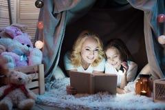 Η γιαγιά και η εγγονή διαβάζουν το βιβλίο στο γενικό σπίτι τη νύχτα στο σπίτι στοκ φωτογραφία