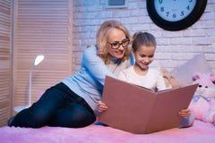 Η γιαγιά και η εγγονή διαβάζουν το βιβλίο τη νύχτα στο σπίτι στοκ εικόνες
