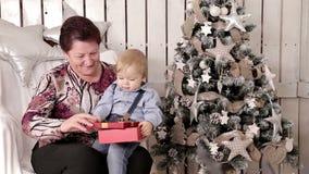 Η γιαγιά και ο εγγονός ανοίγουν ένα κόκκινο δώρο Χριστουγέννων απόθεμα βίντεο