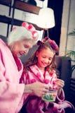 Η γιαγιά και το κορίτσι που επιλέγουν την τρίχα γλιστρούν κάνοντας hairstyle στοκ εικόνες