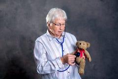 Η γιαγιά με το στηθοσκόπιο είναι γιατρός μαριονετών για τη teddy αρκούδα στοκ εικόνες