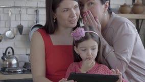 Η γιαγιά, η μητέρα και λίγη κόρη είναι μαζί στο σύγχρονο διαμέρισμα Η συσκευή εκμετάλλευσης κοριτσιών, γιαγιά που ψιθυρίζει επάνω φιλμ μικρού μήκους