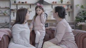 Η γιαγιά, η μητέρα και λίγη κόρη ξοδεύουν το χρόνο καθμένος μαζί στον καναπέ στο διαμέρισμα στούντιο Η στάση κοριτσιών απόθεμα βίντεο
