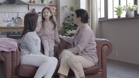 Η γιαγιά, η μητέρα και λίγη κόρη ξοδεύουν το χρόνο καθμένος μαζί στον καναπέ στο σύγχρονο διαμέρισμα Η στάση κοριτσιών φιλμ μικρού μήκους