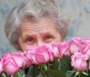 Η γιαγιά πίσω από την ανθοδέσμη ρόδινου αυξήθηκε Στοκ Εικόνες