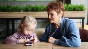 Η γιαγιά φόρεσε τα ακουστικά στην εγγονή της για να ακούσει την ακουστική ιστορία απόθεμα βίντεο