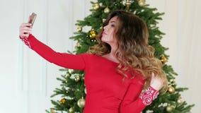 Η γιορτή Χριστουγέννων, κορίτσι του νέου έτους selfie, φωτογραφίστηκε στο υπόβαθρο του χριστουγεννιάτικου δέντρου, ένας όμορφος απόθεμα βίντεο