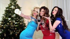 Η γιορτή Χριστουγέννων, όμορφα κορίτσια στα εορταστικά φορέματα, κάνει selfie το κινητό τηλέφωνο, μιλά, γέλιο, τα κορίτσια πίνουν φιλμ μικρού μήκους