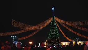 Η γιρλάντα, φω'τα είναι ανοίγει το χριστουγεννιάτικο δέντρο στο κύριο τετράγωνο της πόλης Νέο δέντρο έτους στην πόλη νύχτας απόθεμα βίντεο