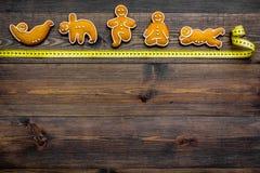 Η γιόγκα για χάνει το βάρος Μέτρηση της ταινίας και των μπισκότων στη μορφή της γιόγκας asans στο σκοτεινό ξύλινο διάστημα αντιγρ Στοκ Φωτογραφία