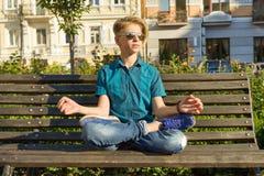 Η γιόγκα στην πόλη, έφηβος κάθεται στο λωτό θέτει στον πάγκο στο πάρκο πόλεων Χαλαρώστε, στηριχτείτε, περισυλλογή στοκ φωτογραφίες με δικαίωμα ελεύθερης χρήσης