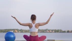 Η γιόγκα υπαίθρια, νέο ελκυστικό κορίτσι γιόγκη στη θέση λωτού meditates και απολαμβάνει το σπιρίτσουαλ calmnes στη φύση φιλμ μικρού μήκους