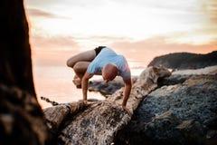 Η γιόγκα Handstand θέτει από το άτομο στην παραλία κοντά στον ωκεανό Στοκ Φωτογραφίες