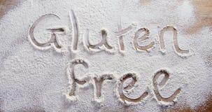 Η γλουτένη λέξης ελεύθερη που γράφει στο ψεκασμένο αλεύρι 4k φιλμ μικρού μήκους