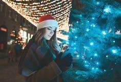 Η γλυκιά γυναίκα σε ένα καπέλο Χριστουγέννων στέκεται σε ένα δέντρο σε μια οδό που διακοσμείται σε διακοπές και χρησιμοποιεί ένα  στοκ φωτογραφία