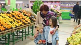 Η γλυκιά καλή γιαγιά με τα μικρά παιδιά αγοράζει τα φρέσκα μήλα στην υπεραγορά απόθεμα βίντεο