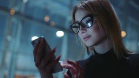 Η γοητεία ξανθή σε μια καλή διάθεση στα γυαλιά με το μαύρο πλαίσιο και τα σκοτεινά ενδύματα είναι στην οδό βραδιού Είναι κοντά απόθεμα βίντεο