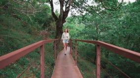 Η γοητεία της λεπτής φίλαθλης κυρίας με τα πανέμορφα ελαφριά ξανθά μαλλιά περπατά κατά μήκος της γέφυρας σιδήρου στο φαράγγι Okat απόθεμα βίντεο