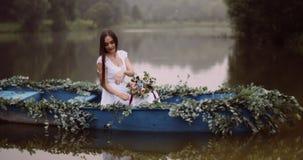 Η γοητεία της νέας γυναίκας στο άσπρο φόρεμα με την όμορφη ανθοδέσμη των λουλουδιών επιπλέει στη βάρκα που διακοσμείται με τα χορ απόθεμα βίντεο