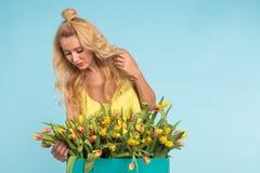 Η γοητεία του ξανθού θηλυκού ανθοκόμου ταξινομεί τις τουλίπες στο κιβώτιο, τις επιλέγει για τη μελλοντική ρύθμιση λουλουδιών στοκ εικόνα