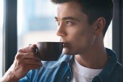 Η γοητεία του χαριτωμένου νεαρού άνδρα απολαμβάνει το espresso Στοκ Φωτογραφίες