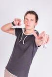 Η γοητεία του όμορφου νεαρού άνδρα σε formalwear κρατά τα χέρια του, δείχνει με τα δάχτυλα στη κάμερα στεμένος το άσπρο υπόβαθρο Στοκ Εικόνα