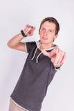 Η γοητεία του όμορφου νεαρού άνδρα σε formalwear κρατά τα χέρια του, δείχνει με τα δάχτυλα στη κάμερα στεμένος το άσπρο υπόβαθρο Στοκ φωτογραφίες με δικαίωμα ελεύθερης χρήσης