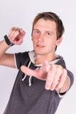 Η γοητεία του όμορφου νεαρού άνδρα σε formalwear κρατά τα χέρια του, δείχνει με τα δάχτυλα στη κάμερα στεμένος το άσπρο υπόβαθρο Στοκ Εικόνες