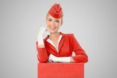 Η γοητευτική αεροσυνοδός έντυσε κόκκινους σε ομοιόμορφο και τη βαλίτσα στοκ φωτογραφία