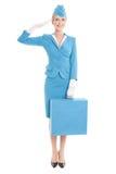 Η γοητευτική αεροσυνοδός έντυσε μπλε σε ομοιόμορφο και τη βαλίτσα στο λευκό στοκ εικόνες