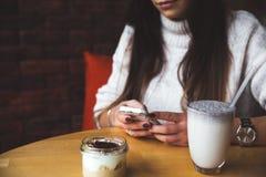 Η γοητευτική γυναίκα κοιτάζει στο τηλέφωνο στον καφέ Νόστιμοι κέικ και καφές σοκολάτας στον πίνακα Φωτεινό ηλιόλουστο πρωί στον κ Στοκ εικόνες με δικαίωμα ελεύθερης χρήσης