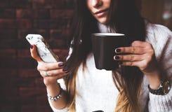 Η γοητευτική γυναίκα κοιτάζει στο τηλέφωνο στον καφέ Νόστιμοι κέικ και καφές σοκολάτας στον πίνακα Φωτεινό ηλιόλουστο πρωί στον κ Στοκ Φωτογραφίες