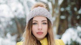 Η γοητευτική γυναίκα με τα μπλε μάτια στέκεται στο χειμερινό καπέλο στο δάσος που καλύπτεται με το χιόνι Πορτρέτο της απόλαυσης κ απόθεμα βίντεο