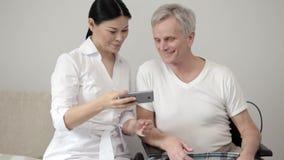 Η γοητευτική γυναίκα νοσοκόμα παίρνει selfie με το με ειδικές ανάγκες ασθενή απόθεμα βίντεο