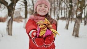 Η γοητευτική νέα μαθήτρια κρατά χαρωπά στα χέρια της ένα συσκευασμένο κιβώτιο με ένα δώρο στο χειμερινό δάσος μέσα απόθεμα βίντεο
