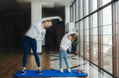 Η γοητευτική οικογένεια ξοδεύει το χρόνο στη γυμναστική Στοκ Φωτογραφία