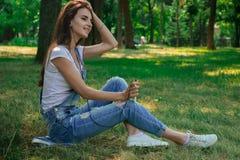 Η γοητευτική όμορφη συνεδρίαση κοριτσιών στη χλόη στο πάρκο και ακούει τη μουσική Στοκ φωτογραφία με δικαίωμα ελεύθερης χρήσης