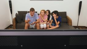 Η γοητευτικοί οικογένεια, mom, ο μπαμπάς, η κόρη και ο γιος προσέχουν τη TV στο καθιστικό από κοινού απόθεμα βίντεο