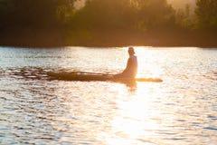 Η γουλιά surfer κάθεται στον πίνακα γουλιάς στο χρυσό φως Στοκ εικόνες με δικαίωμα ελεύθερης χρήσης