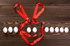 Η γραμμή από τα αυγά Πάσχας και το λαγουδάκι κουνελιών Πάσχας που γίνεται από την κόκκινη ερυθρά κορδέλλα είναι στο ξύλινο υπόβαθ Στοκ Φωτογραφίες