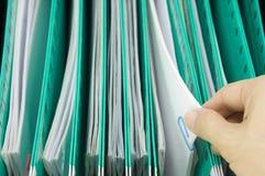 Η γραφική εργασία επιλογών ατόμων από τον πράσινο φάκελλο αναστολής κρεμά στο γραφείο Στοκ φωτογραφία με δικαίωμα ελεύθερης χρήσης