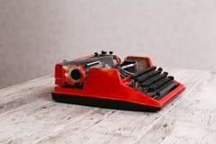 Η γραφομηχανή είναι κόκκινη με το έγγραφο σε το και για τον πίνακα Στοκ Φωτογραφία