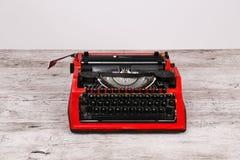 Η γραφομηχανή είναι κόκκινη με το έγγραφο σε το και για τον πίνακα Στοκ Εικόνες