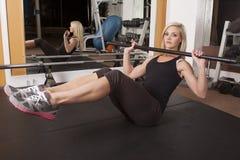 Η γυμναστική γυναικών κάθεται επάνω με το φραγμό Στοκ Εικόνες