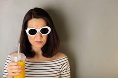 Η γυναίκα άσπρα ριγωτά τοπ και άσπρα γυαλιά ηλίου πίνει το πορτοκάλι Στοκ Φωτογραφίες